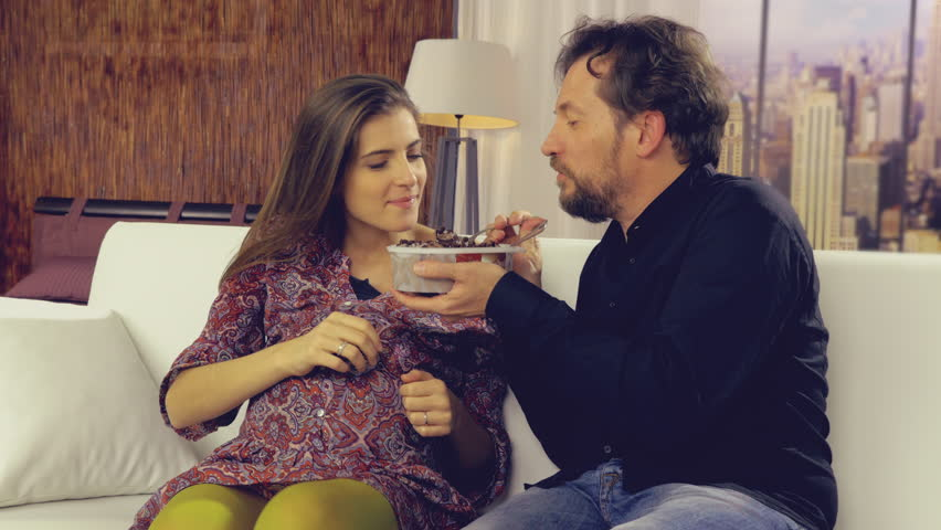 Husband bringing icecream to pregnant happy wife