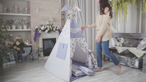 Woman made Child's toy Tepee tent of native american made of canvas. room in the house with the tepee. Playroom for kids with Teepee or DIY tent, decorated flags. wigwam for children in a room.