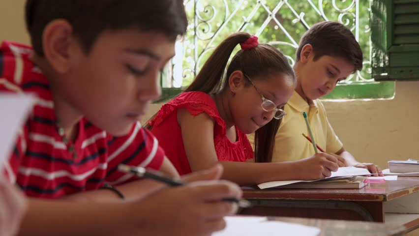 Young people and education. Group of hispanic students in class at school during lesson. Boys and girls with papers for admission test, examination