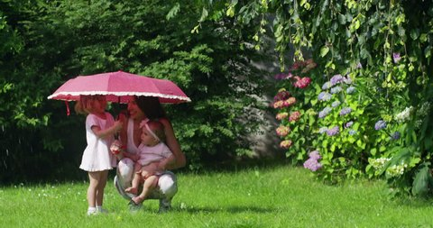 Cinemagraph of a mother with daughters playing and smiles in the rain despite the sunny day. Concept: family, play, love and nature.