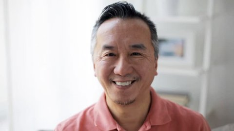 face of happy smiling asian man at home