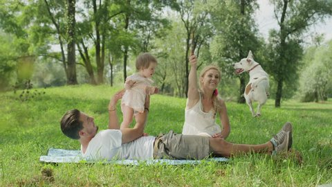 SLOW MOTION CLOSE UP DOF: Pretty young woman sitting on the blanket in park with her husband and baby daughter and playing with Jack Russell dog teasing him with a stick. Quality family time in nature