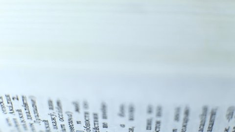 Fast flipping pages of thick book close up