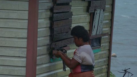 FIJI - DEC 17 2016:Fijian woman boarding up her house during a Tropical Cyclone. On Feb 2016 Severe Tropical Cyclone Winston was the strongest tropical cyclone in Fiji in recorded history.