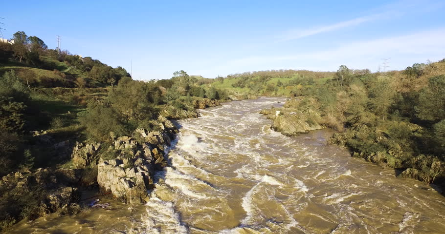 4k Raging American river during floods in 2017, white water on the American river in Northern California, and people watching from a bridge