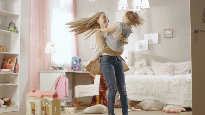 Young Sweet Mother Holds Her Little Cute Daughter in Arms and Spins with Her. Children's Room is Pink and Full of Toys. Slow Motion. Shot on RED EPIC-W 8K Helium Cinema Camera.