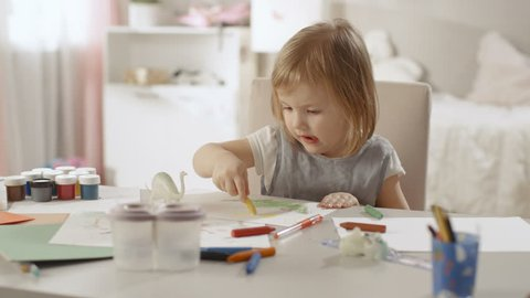 Cute Little Girl Sits at Her Table and Draws with Crayons. Her Room Is Pink, Pretty Drawings Hanging on the Walls, Many Toys Lying Around. Shot on RED EPIC-W 8K Helium Cinema Camera.