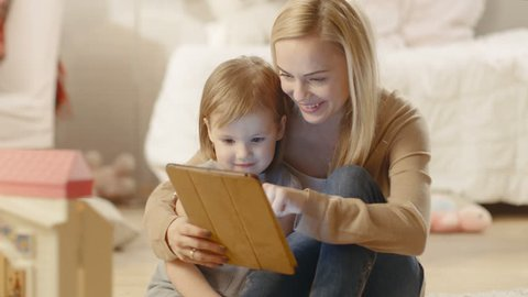 Beautiful Mother and Her Little Daughter Have Good Time Reading Children's Books on a Tablet Computer. Children's Room is full of Toys. Shot on RED EPIC-W 8K Helium Cinema Camera.