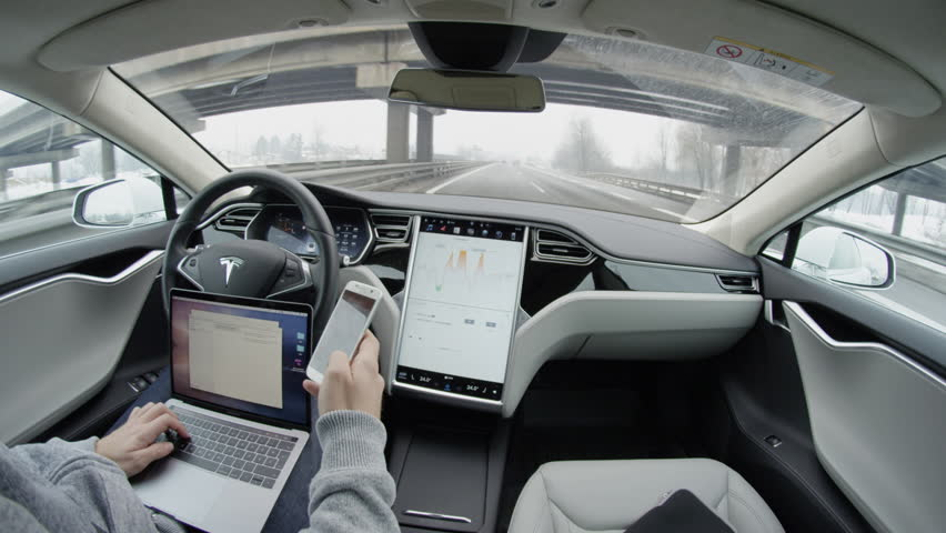 LJUBLJANA, SLOVENIA - FEBRUARY 4, 2017: Business correspondence via smartphone and laptop from the car while traveling in self-driving autonomous automated driverless Tesla Model S electric vehicle