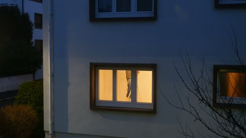 Home jobe decoration - Working late concept of man redecorating painting the new apartment - view from the street at dusk