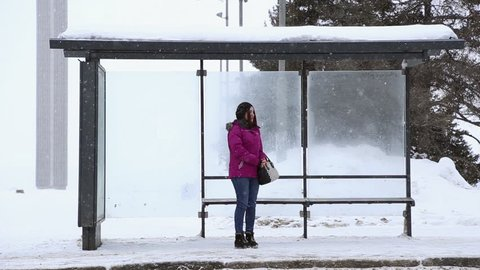 SAMARA, SAMARA REGION/RUSSIA - FEBRUARY 18: A girl stands at the bus stop in winter, she's waiting for the bus, it's snowing on February 18, 2017 in Samara