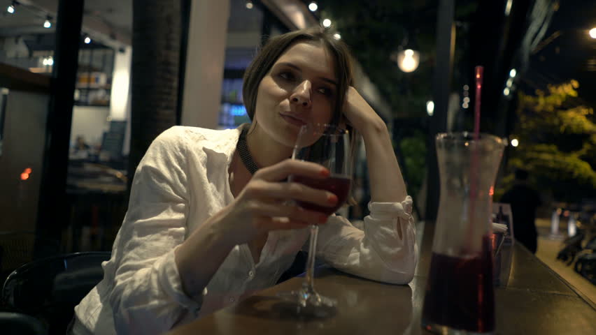 Pensive woman drinking red wine sitting in cafe at night  | Shutterstock HD Video #24280973