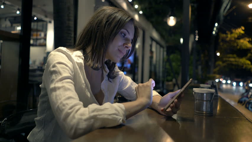 Young woman texting on smartphone sitting in cafe at night  | Shutterstock HD Video #24281063