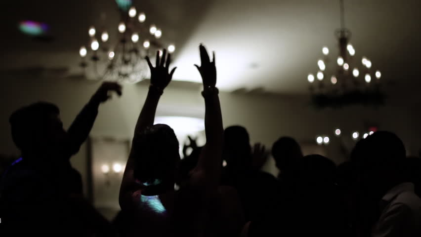 Group of silhouetted people dancing in a dark banquet hall for a wedding reception