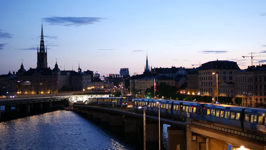 Old town cityscape skyline Stockholm, Sweden. Subway trains passing by over elevated railway bridge at night. Gamla stan city | Shutterstock HD Video #24299963