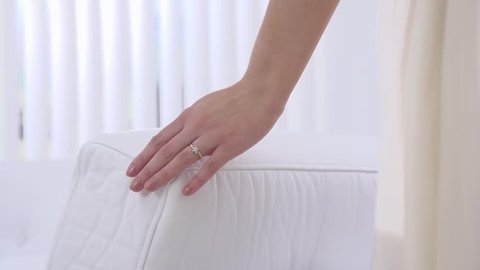 Young beautiful girl touches hand couch. A gentle touch of a hand on a white pillow in slow motion. Slow motion family home part 8 of 15.