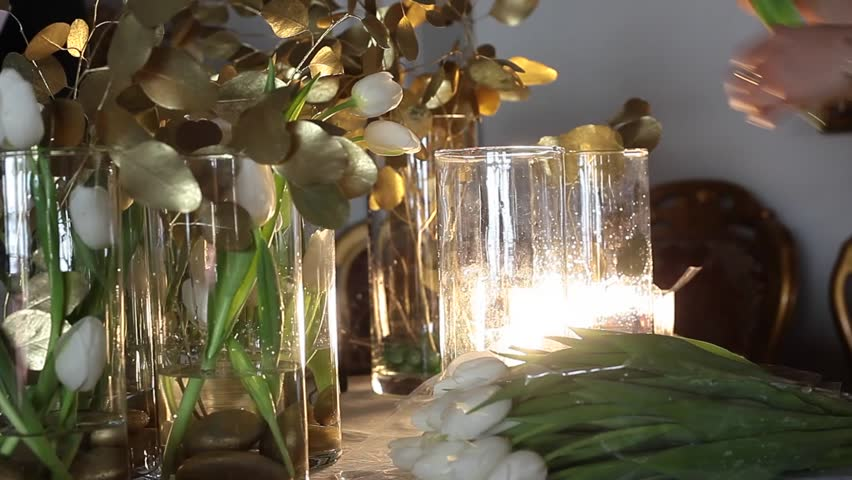 Florist at work. White Tulips in Clear Glass Vases, Golden Flowers on the Table #24324689