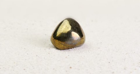 Pyrite gem rotating on white sand surface. Semi precious gemstone. Clip contains seamless loop.