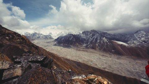Male trekker enjoys great Cho Oyu mountain and Everest massif from Gokyo Ri peak. Amazing clouds above the Nepal Himalaya