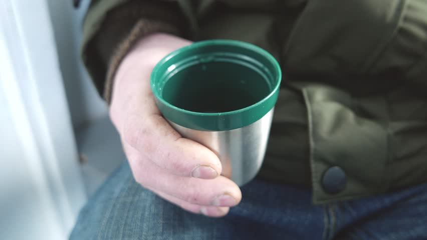 Man holding a stainless steel cup with tea outside during winter. | Shutterstock HD Video #24338573