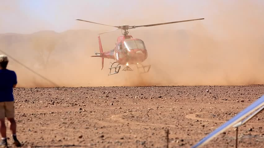 morocco- helicopter descends to the ground kicking up dust around them in the desert #24354773