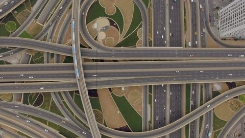 aerial view of road junction with moving cars and railway tracks on which the train rides. The concept of the urban form of Dubai, UAE