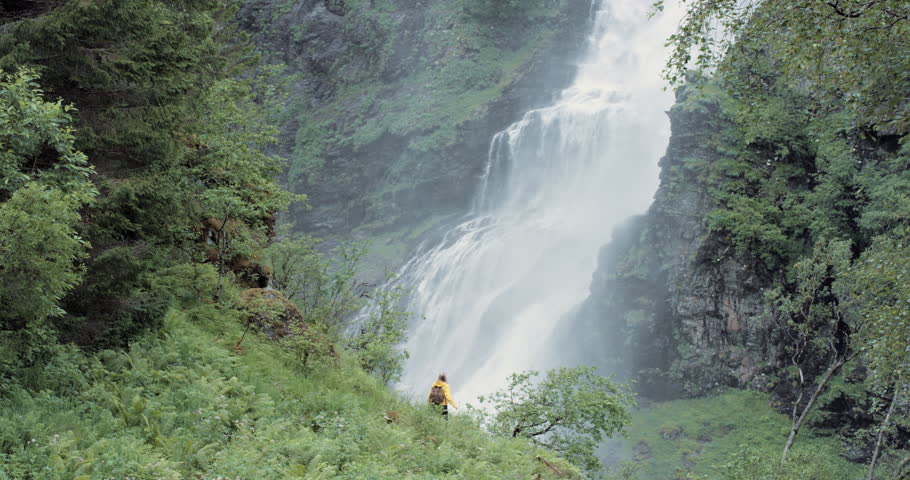 Woman lifting arms up arms raised in front of waterfall wearing yellow jacket scenic landscape nature background view enjoying vacation travel adventure in Norway | Shutterstock HD Video #24369683