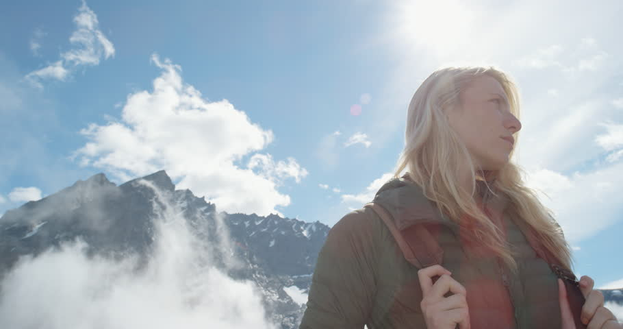 Close up portrait of Woman Climber at top of mountain in nature with blonde hair blowing in wind above the clouds view Hiker Girl trekking in Romsdalen Valley Norway Slow Motion
