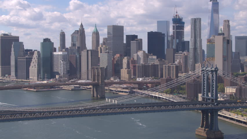 AERIAL: Beautiful view of iconic downtown New York skyscrapers, office buildings and Brooklyn and Manhattan Bridges across East River. Amazing New York City skyline cityscape on a gorgeous sunny day