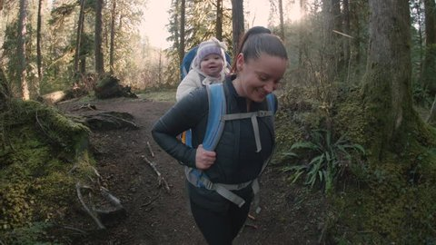 Happy Mom and Baby Daughter in Hiking Backpack Walking Down Forest Trail on Sunny Day