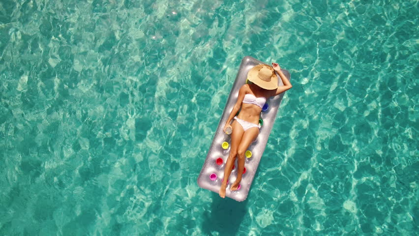 Aerial - Young woman enjoying summer on inflatable mattress in crystal clear water