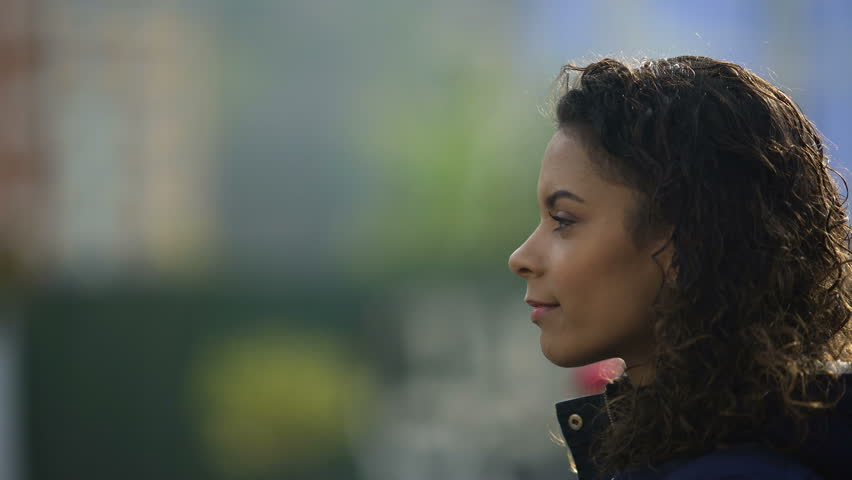 Beautiful biracial young lady portrait in profile, inspired woman model smiling