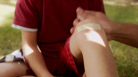 A father putting on a plaster on the knee of his son