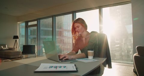 business woman in modern office skyscraper in the works at the table, a sunny day, the sun glare, laptop, tablet, mobile phone use in situation