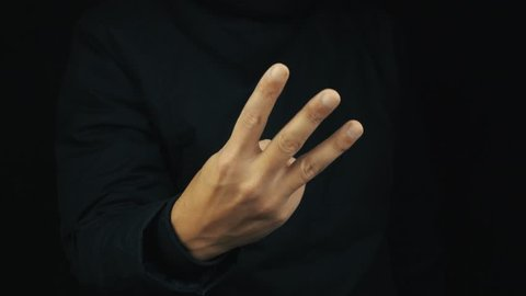 Caucasian male hand in long sleeve jacket unbend fingers making counting gesture sign on black backround, close up isolated