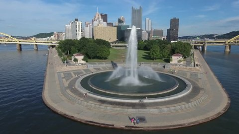 Downtown Pittsburgh Point State Park Fountain on the Confluence of the Three Rivers  Aerial 4K with the Downtown Skyline as a Backdrop on a Blue Sky Sunny Day