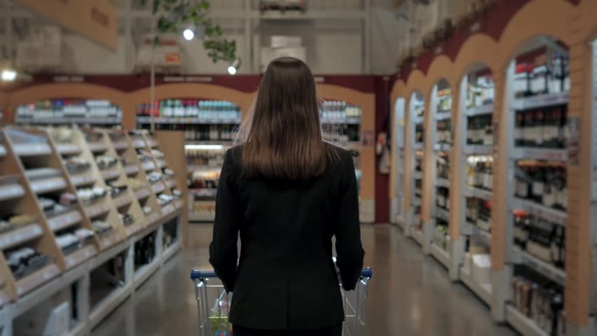 Woman shopping at the supermarket, follow shot from back of young woman with trolley in shopping center, alcohol store. | Shutterstock HD Video #24490103