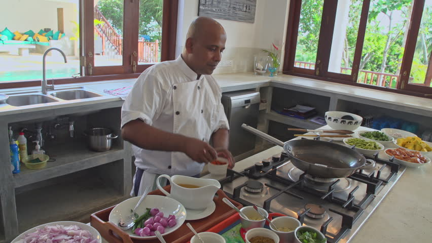 Wide Shot Of A Sri Lankan Chef Adding Spices To Frying Pan As He Prepares