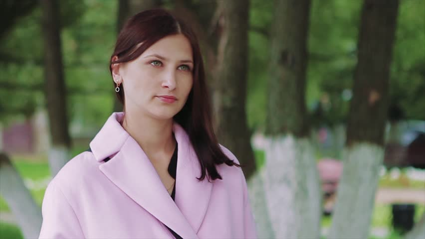 Beautiful Young Girl in a Pink Coat With Concentration Looks Ahead. Her Burgundy Hair Stacked on the Left Shoulder. is Visible on the Right Ear Earring. in the Background Neat Rows of Park Trees. | Shutterstock HD Video #24518873
