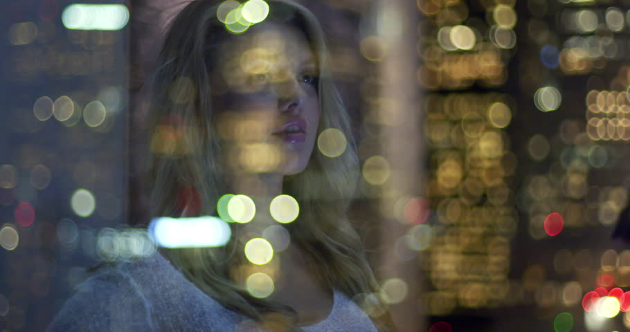 Beautiful young blonde woman reflected in a window as she laughs while looking out at Downtown Los Angeles at night. Close up, hand held.