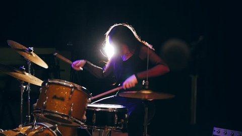 Flowing black hair - beauty girl plays drum rock at garage, slow-motion