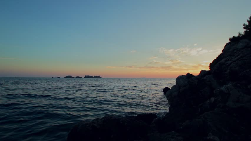 Waves Crashing On Rocks At Sunset