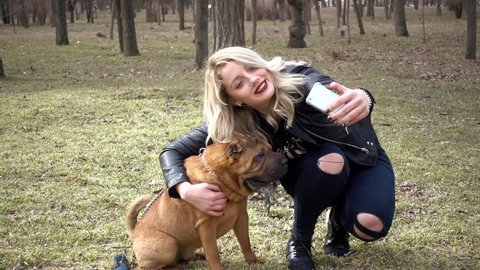 KHERSON, UKRAINE - MARCH 03, 2017: Young Woman taking Photo Selfie with Mobile Phone Playing Sharpei Dog In Spring Park
