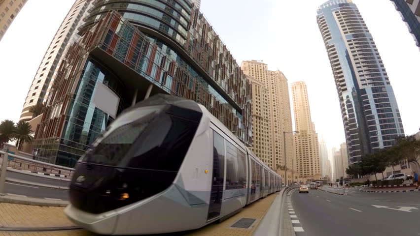 Modern tram rides on rails among the skyscrapers...