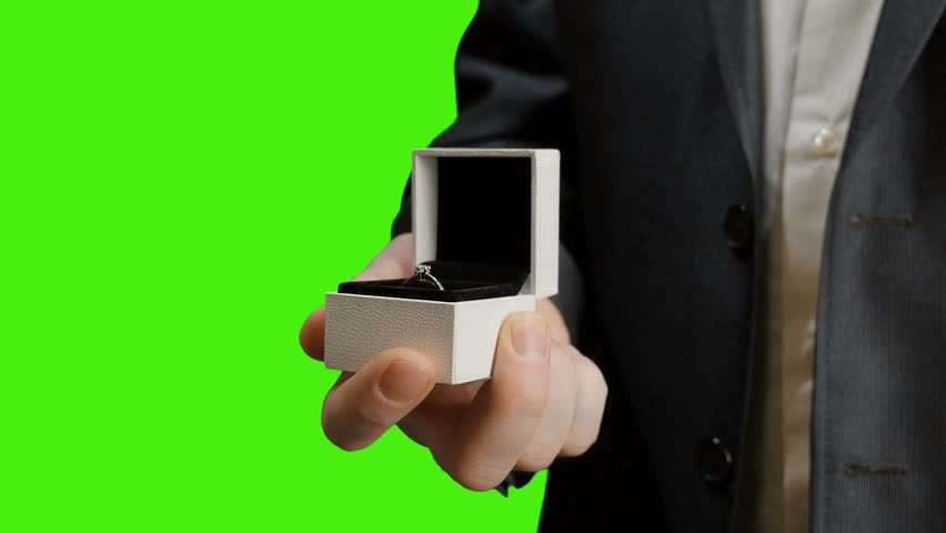 The groom opens the box with a wedding ring. Green screen.