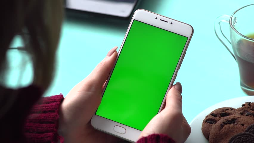 Beautiful girl holding a smartphone in the hands of a green screen green screen, hand of man holding mobile smart phone with chroma key green screen on white background, new technology concept | Shutterstock HD Video #24608522