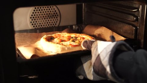 opening oven and taking out a pizza