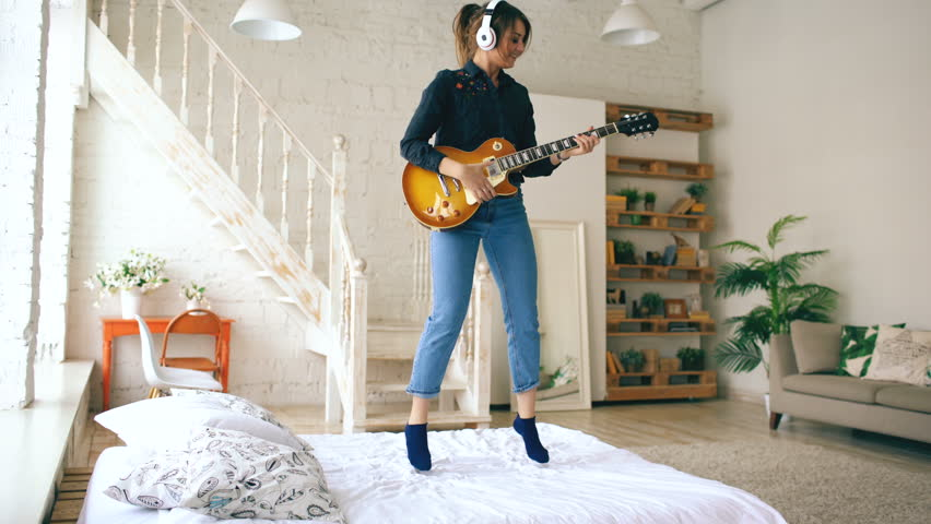 Funny young woman in headphones jumping on bed with electric guitar in bedroom at home indoors