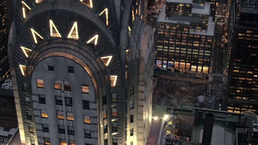 AERIAL HELI SHOT: Flying past lit with lights iconic Chrysler Building rising above modern office buildings and busy crowded New York streets after the sunset. Industry machinery in construction pit