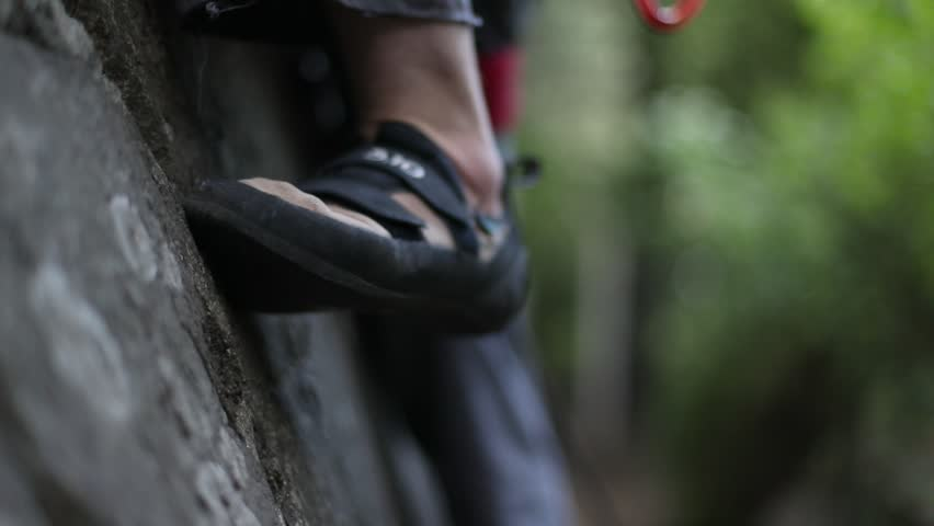 Rock climbing detail of climbers shoes on straight vertical wall. Slow motion 120fps detail close up. Extreme risk outdoor sport. Patagonia Argentina.